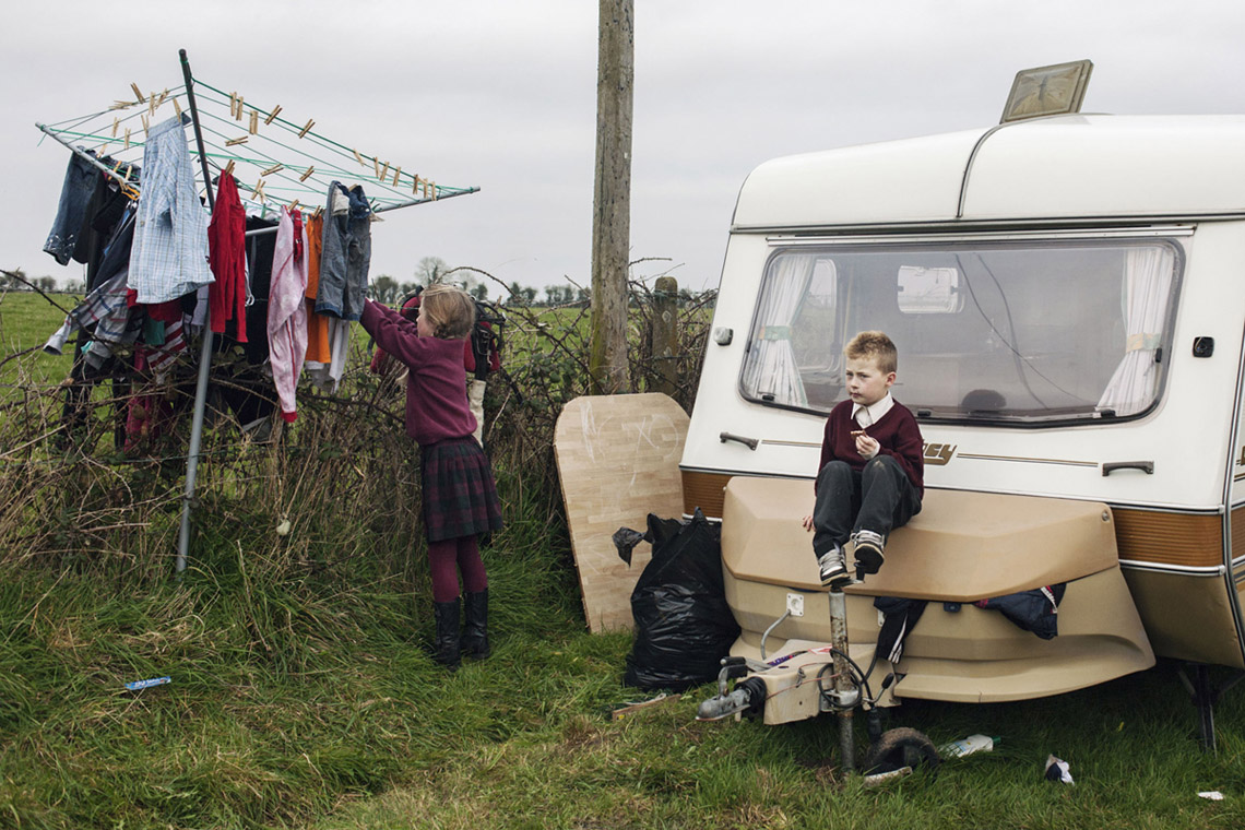 Birte Kaufmann, from The Travellers; Pamela is hanging clothes on the dryer and Jimmy is sitting on top of the camper box